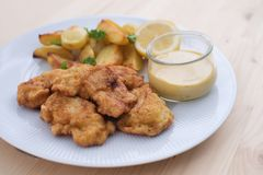Cod fish in batter or cod fritters served with baked potatoes with parsley leaves and home made mayonnaise sauce. Stock Photo