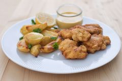 Cod fish in batter or cod fritters served with baked potatoes with parsley leaves and home made mayonnaise sauce. Stock Photos