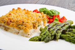 Cod fish with crispy breadcrumbs and asparagus. A cod fish with crispy breadcrumbs and asparagus Stock Photography
