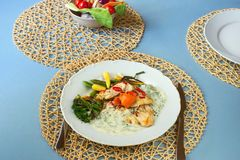 Cod fish, dill sauce and vegetable garnish. Cod fish with dill sauce and vegetable garnish. Portion on plate, bottle with salad on blue table with bamboo place Royalty Free Stock Photo