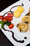 Cod fish dish with lemons and tomatoes. A tasty dish of grilled cod fish served with lemons, tomatoes and potatoes on white plate, dark table setting. Whole Royalty Free Stock Image
