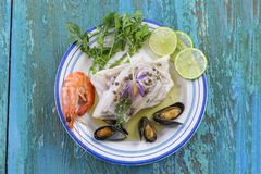 Cod fish fillet, Atlantic cod with seafood mussells,shrimps,lime and vegetable, on blue wooden background Stock Photography