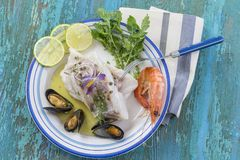 Cod fish fillet, Atlantic cod with seafood mussells,shrimps,lime and vegetable, on blue wooden background Stock Images