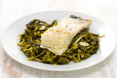 Cod fish with greens on plate Royalty Free Stock Photography