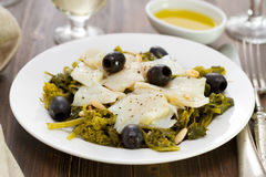 Cod fish with olives and greens on white plate Royalty Free Stock Image