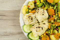 Cod fish on plate with vegetables Stock Photo