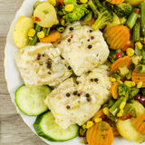 Cod fish on plate with vegetables Royalty Free Stock Photography