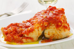 Cod fish with tomato sauce on white dish Royalty Free Stock Photography