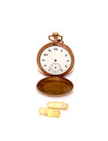 Cod liver oil omega 3 gel capsules in front of vintage pocket clock Royalty Free Stock Images