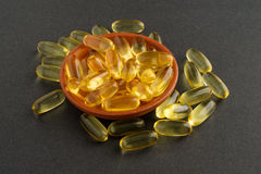 Cod liver oil pills in small dish Royalty Free Stock Photo