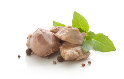 Cod liver. Some pieces of cod liver with fresh green basil on the white plate stock images