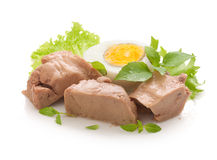 Cod liver. Three pieces of cod liver with fresh green lettuce, basil and boiled egg on the white plate royalty free stock image