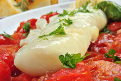 Cod loins with tomato on a plate Royalty Free Stock Photos