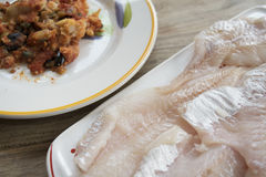 Cod with olives capers and tomato sauce Stock Photos