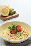 Cod roe noodles with bacon cream on bowl with lemon and herbs royalty free stock photos