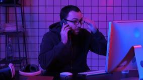 Codage du spécialiste dans occasionnel avec l'ordinateur et parler par le téléphone tout en codant l'information pour créer le lo photo stock