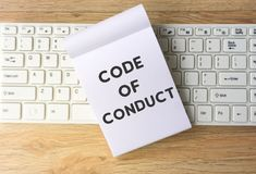 Code of Conduct. On notepad on top of computer keyboard, wooden table background. Retro style effect Royalty Free Stock Photo