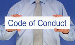 Code of conduct. Text 'Code of Conduct' in blue letters written on a white card held by a businessman wearing a pale blue shirt and gray tie, blue background Stock Image