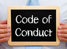 Code of conduct. Written in white chalk on framed blackboard held by businessman wearing suit Stock Photo