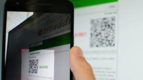 Code du balayage QR avec le téléphone portable à partir de l'ordinateur et paiement avec le bitcoin dans la boutique banque de vidéos