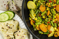 Code fish on plate with vegetables on frying pan Stock Image