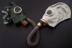 Codependent Relationship, Negative Emotions, Hazardous Affair And Toxic Love Concept With Two Gas Masks Connected On The Same Hose Stock Photo