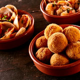 Codfish bacalao croquettes. Covered in bread crumbs and fried served with steamed spicy Venus shell clams in individual bowls for Spanish tapas Royalty Free Stock Image