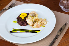 Codfish with black rice and sauce Stock Images