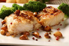 Codfish - fish fillet in sauce with garlic and vegetables Royalty Free Stock Photos