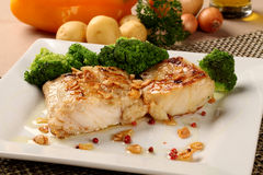 Codfish - fish fillet in sauce with garlic and vegetables Stock Images