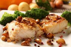 Codfish - fish fillet in sauce with garlic and vegetables Royalty Free Stock Images