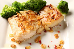 Codfish - fiskfilé i sås med vitlök och grönsaker Royaltyfri Bild