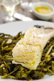 Codfish with olives and greens on white plate Stock Photos
