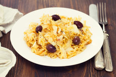 Codfish with potato chips on white plate. Codfish with potato chips and olives on white plate Stock Image