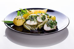 Codfish with potatoes and fennel. A tasty homemade meal, healthy and very tastefull. Served on a black dish on a white background Royalty Free Stock Image