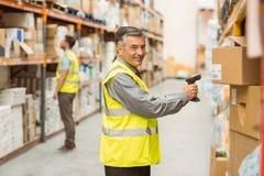 Codice a barre di esame del lavoratore del magazzino sulla scatola immagine stock libera da diritti