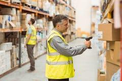 Codice a barre di esame del lavoratore del magazzino sulla scatola immagini stock
