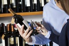 Codice a barre di esame delle coppie sulla bottiglia di vino con Smartphone fotografia stock