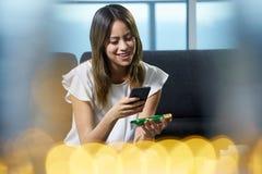 Codice a barre di ricerche della donna sul pacchetto dell'etichetta dell'alimento con il telefono Immagine Stock