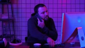 Codificación del especialista en casual con el ordenador y el hablar por el teléfono mientras que cifra la información para crear almacen de metraje de vídeo