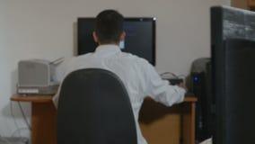 Codificación joven hermosa del programador en dos ordenadores almacen de metraje de vídeo