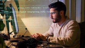 Codificación masculina joven del programador en la noche almacen de metraje de vídeo