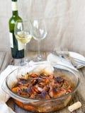 Codorniz fritadas deliciosas com vegetais - alho, cenouras, cebolas, cozidas em um formul?rio de vidro, na garrafa do vinho branc foto de stock royalty free