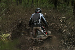 Cody mud 1. A man rides through a huge muddy puddle on a quad bike in the rain Stock Photography