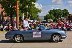 Cody, Wyoming, EUA - U S Senador John Barrasso e sua equitação de Bobbi da esposa em um convertible e ondulação quando parti imagens de stock royalty free