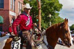 Cody Wyoming, USA - cowboyen med ljus röd skjortaridning på självständighetsdagen ståtar Royaltyfria Foton