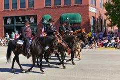 Cody, Wyoming, USA - Juli 4th, 2009 - fyra ryttare iklädda svarta visande Wyatt Earp, Virgil Earp, Morgan Earp och Doc Holliday Royaltyfri Bild