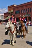 Cody Wyoming, USA - Juli 4th, 2009 - två ryttare hälsar åskådarna, medan rida med självständighetsdagen, ståtar Royaltyfria Bilder