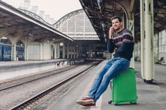 Codzienny styl życia pojęcie Przystojny mężczyzna jest ubranym pulower i cajgi, pozy przy sztachetowej stacji platformą, chudy pr fotografia stock
