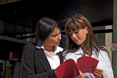 Coeds looking at a file. Portrait of two students looking at a file together Royalty Free Stock Image